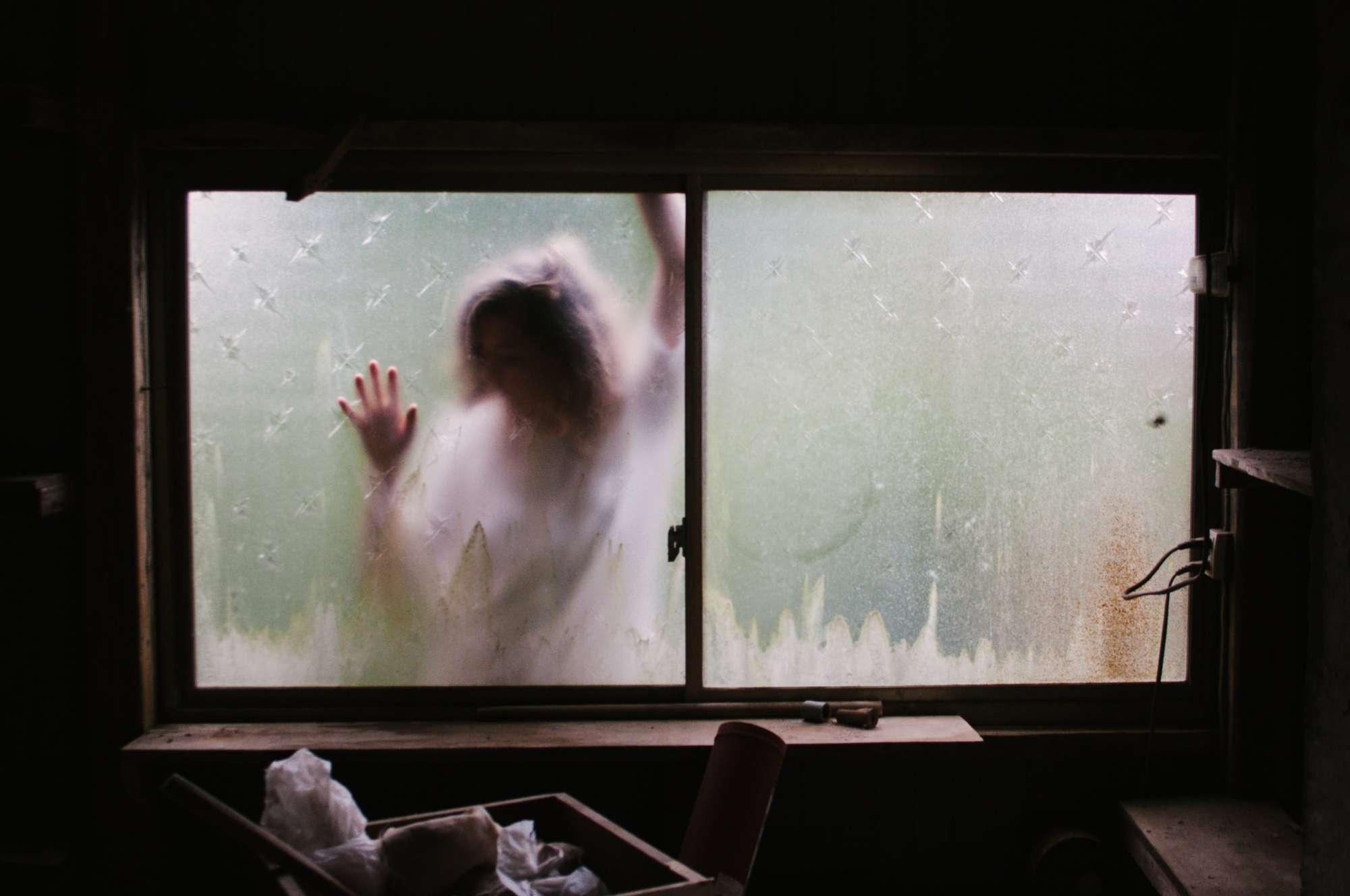 Woman behind a blurry window