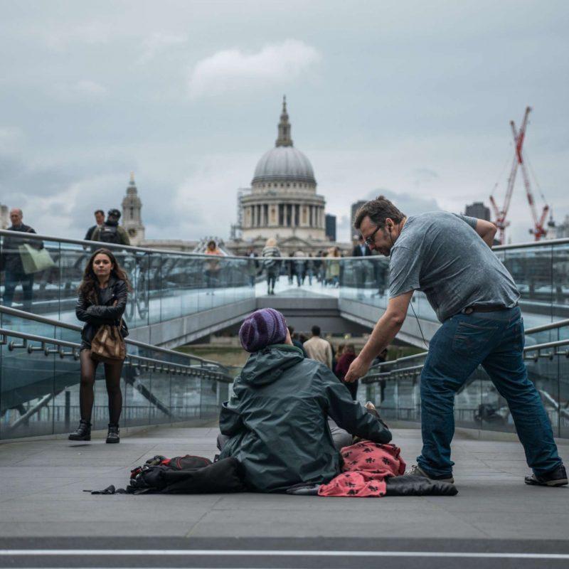 A man handing money to a homeless individual