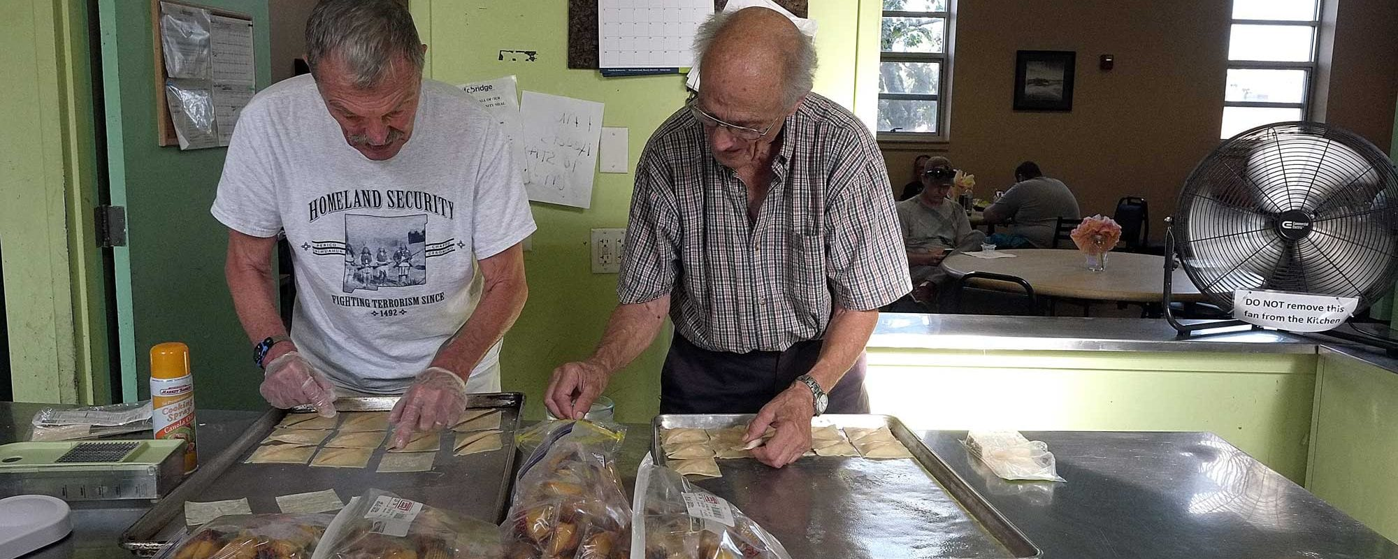 two men helping with community meals