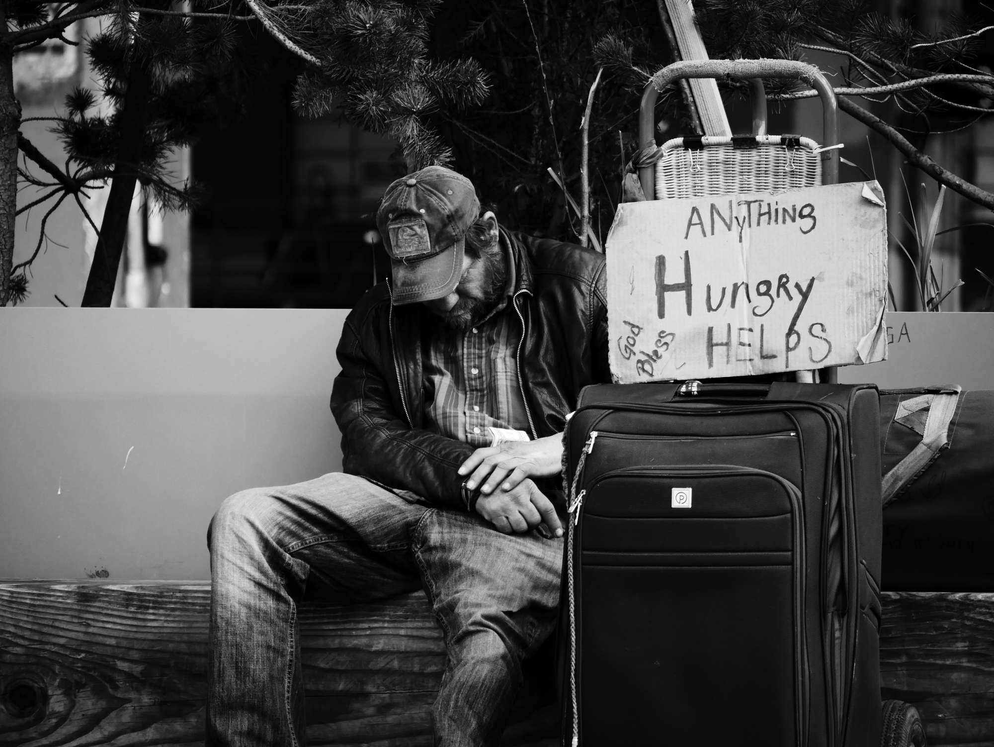 Homeless man holds Hungry sign