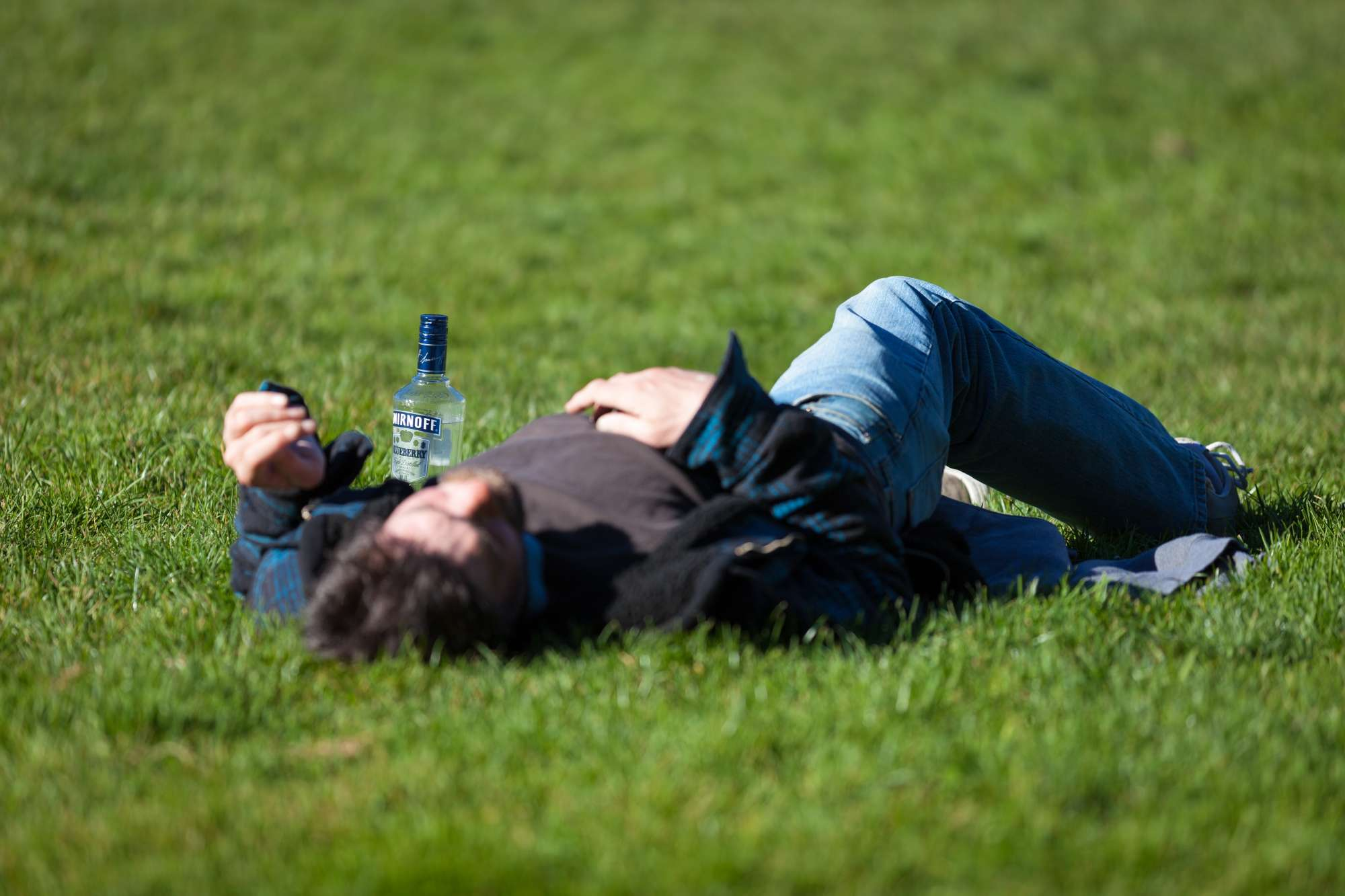 Drunk man laying in grass