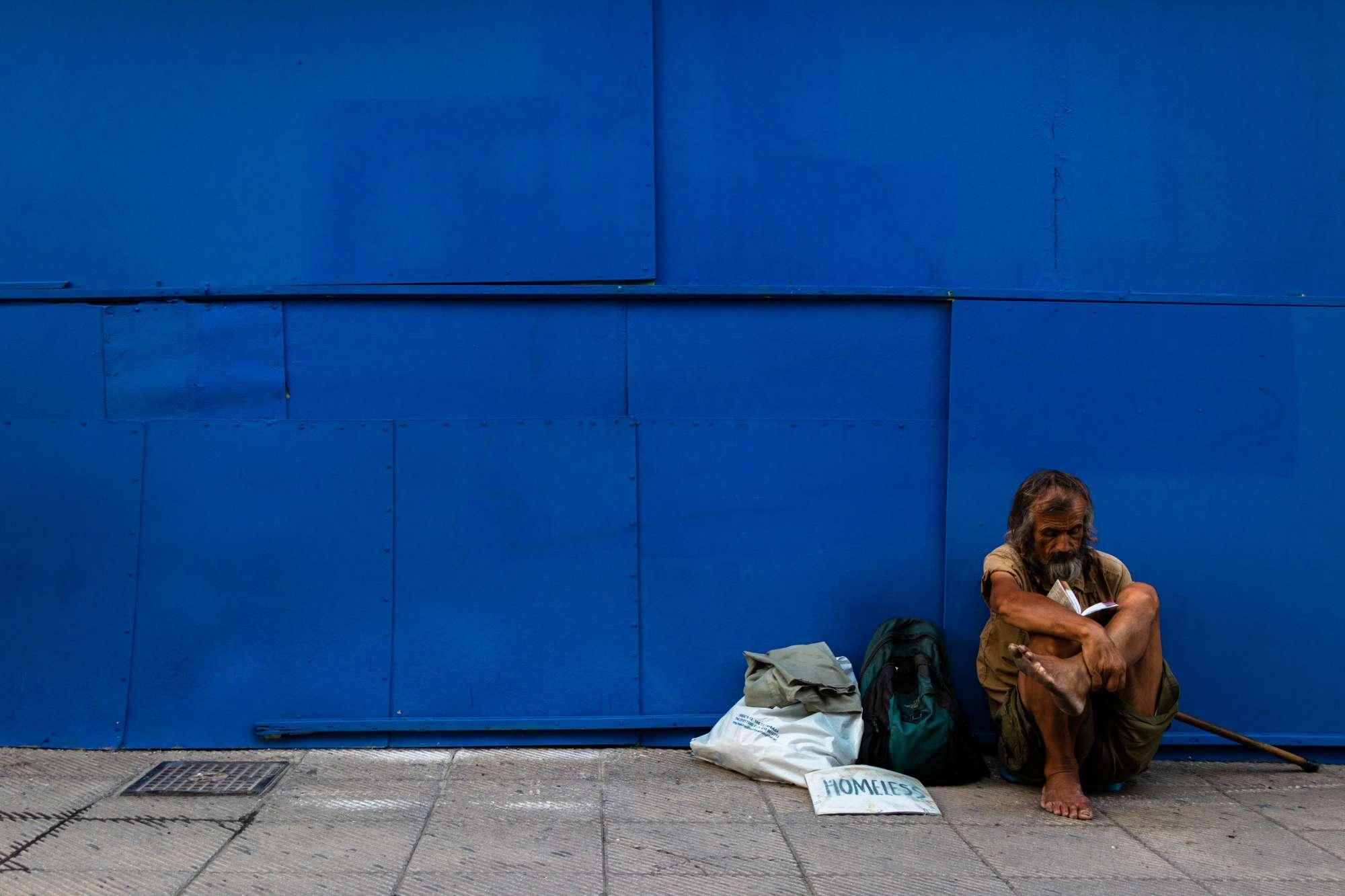 Homeless man sitting on blue wall