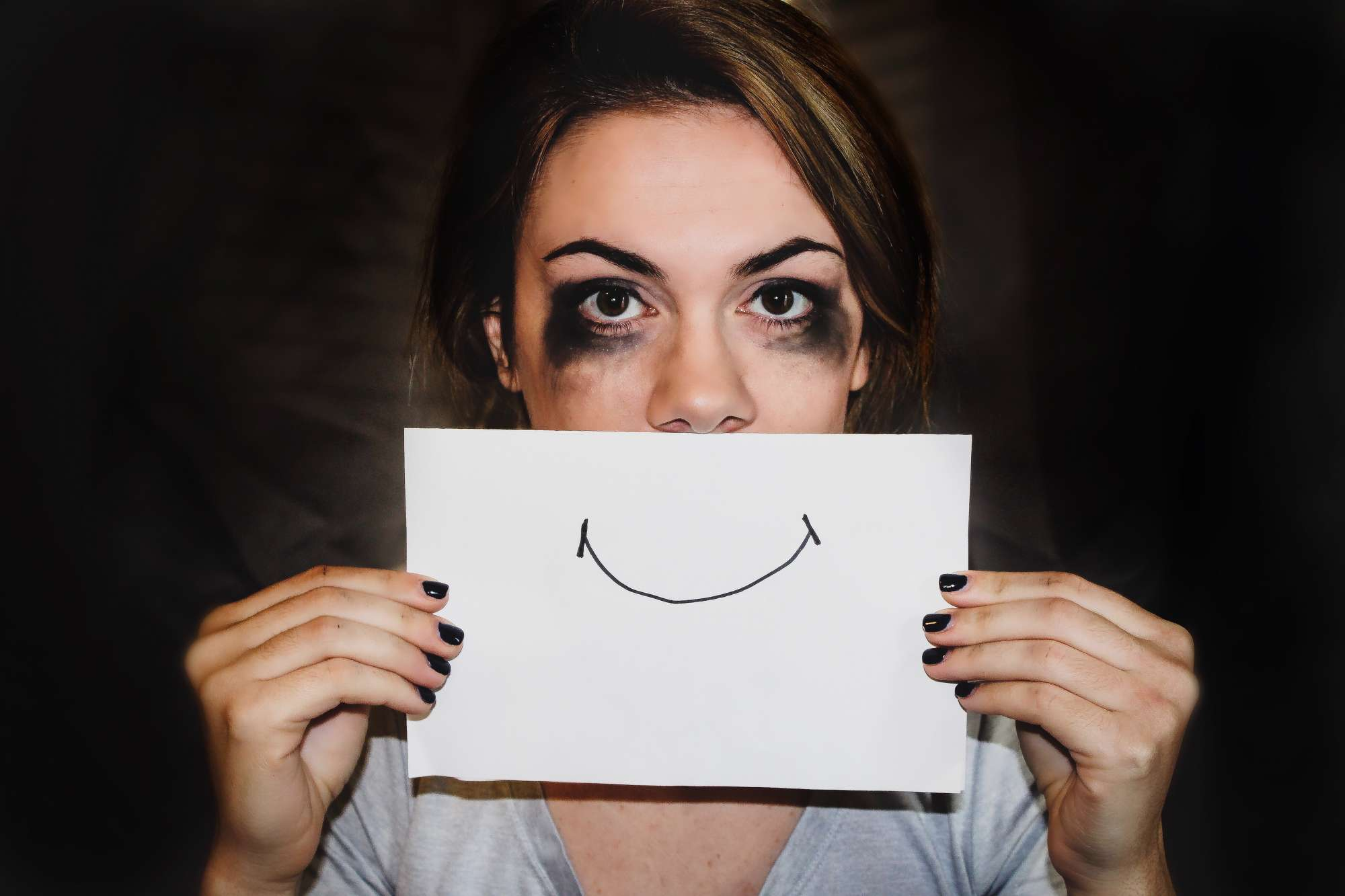 Woman holding a sad face on paper