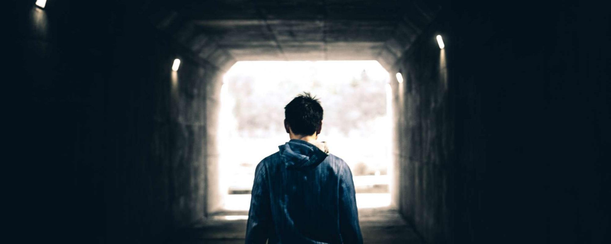 Boy walking in tunnel